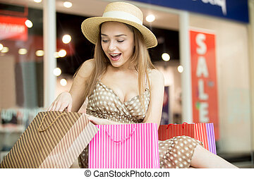 Happy shopping woman looking at her purchase - Excited young...