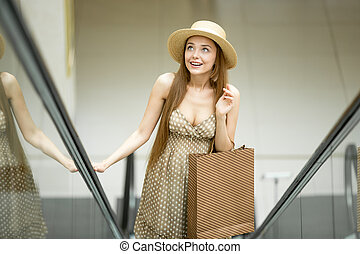 Excited woman in shopping centre standing on escalator