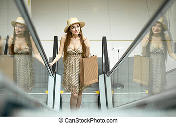 Woman in shopping centre standing on escalator