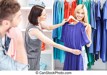 Blond girl choosing clothes in store