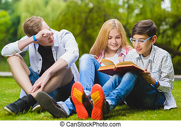 Smiling kids having fun and reading book at grass. Children playing outdoors in summer. teenagers communicate outdoor