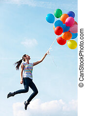 Flying - Image of young woman with colorful balloons flying