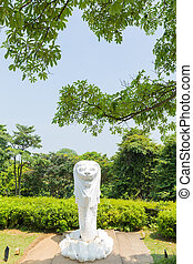 Merlion statue in park. in park tree near and top mountain.