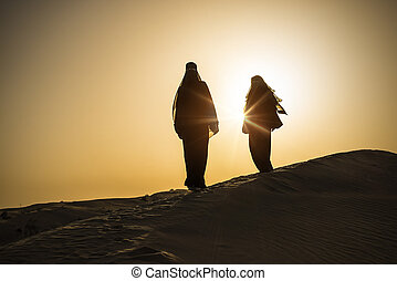 desert woman sun - two traditional clothed women standing on...