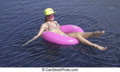 Woman swimming in inflatable ring - Pretty young woman...