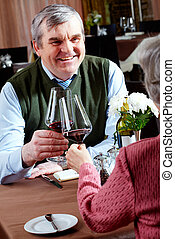 Cheers - Image of senior couple having dinner at a...