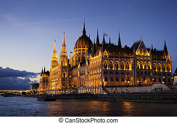 Hungarian Parliament Building along Danube River at night,...