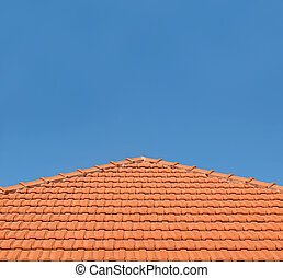 Tiled Rooftop on Blue Sky - An orange-tiled rooftop against...