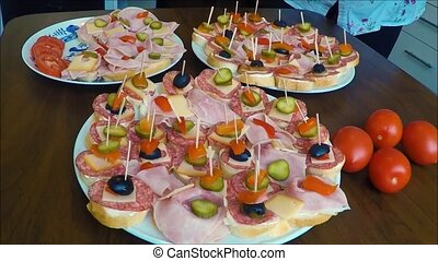 Sandwiches (canapes) of salami on a plate