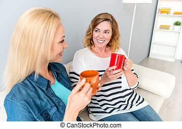 Cute family chatting with beverage at home
