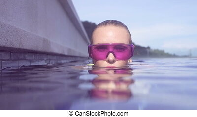 Woman in purple sunglasses in pool.