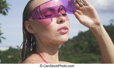 Face of woman in purple sunglasses.
