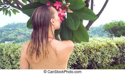 Bikini woman smelling flower. - Sexy young woman wearing...