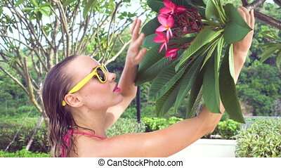 Bikini woman smelling flower.