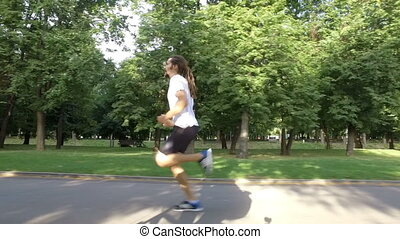 Healthy man running outdoors in park on road - Healthy man...