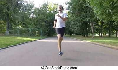 Healthy man running outdoors in park on road