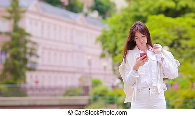 Portrait of beautiful woman using smartphone outdoors -...