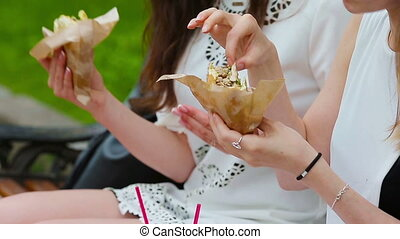 Caucasian women eats hamburger fast food sandwich on the...