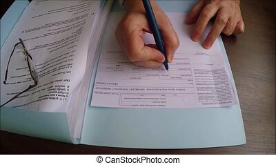 Using a pen to fill out a lottery slip to play the lotto