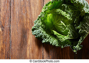 Green savoy cabbage - Raw savoy cabbage on a wooden...