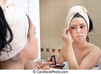 Girl apllying make up in bathroom - Pretty young woman with...