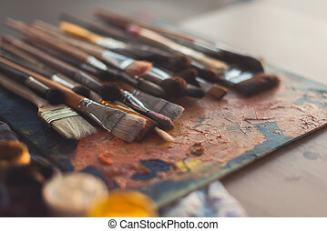Different size paintbrush collection on an old palette with...