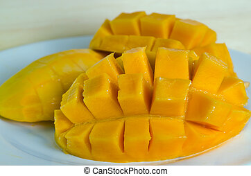 Mango nicely cut on the plate on wooden background (Also known as horse mango, Mangifera foetida, Anacardiaceae, Mangifera, M. indica)
