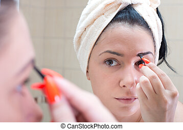 Girl applying makeup on eyebrows - Pretty young woman with...