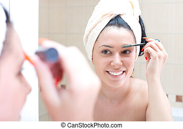 Girl make up in bathroom - Pretty young woman with towel on...