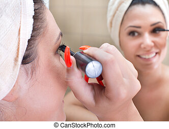 Girl applying mascara in bathroom - Pretty young woman with...