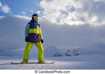 snowboarder standing on the board in the mountains of...