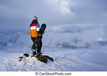 Snowboarder standing a rock on edge cliff - Snowboarder...