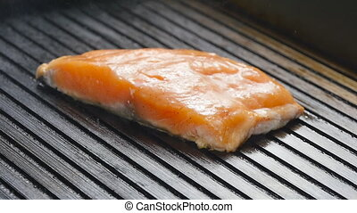 Grilled red fish steak salmon on the grill pan, closeup view