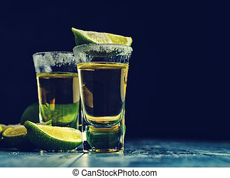 Mexican Gold Tequila with lime and salt on wooden table,...