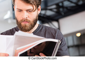 Casual bearded businessman reading document paper close up...