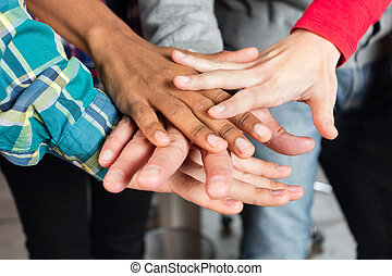 Diverse people team hands on top of each other support...