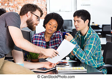 Man holding paper showing colleagues business people office...