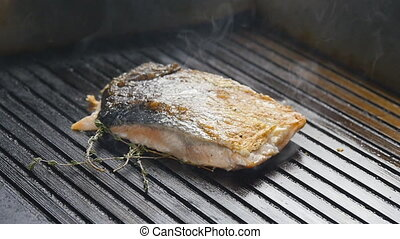 Grilled red fish steak salmon on the grill in slow motion -...