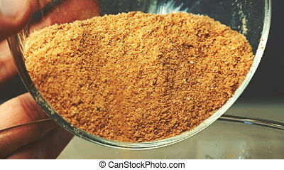 Close-up view of breadcrumbs and spices mixed together pours...