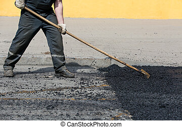 Road worker leveling fresh asphalt during asphalt pavement...