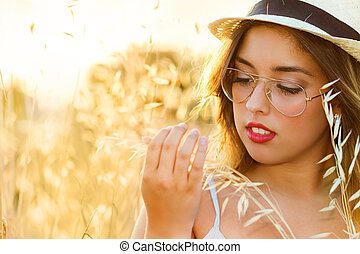 Teen girl touching wheat in field.