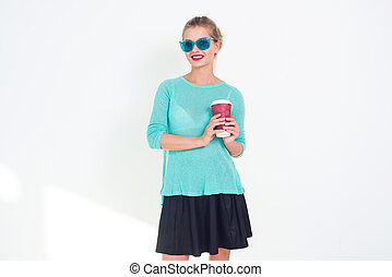 Beautiful female holding cup of hot coffee to go, wearing...