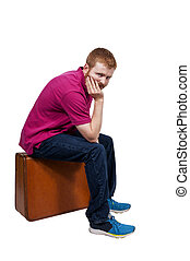 Man on Vacation - Young man going on vacation sitting on a...
