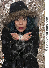 Woman Blowing Snow - Beautiful woman blowing snow off of her...
