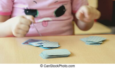 The child plays the playing cards at the table in the...