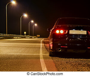 black car on the road at night