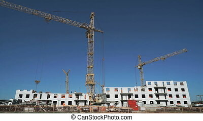 Three construction cranes working on the site - The...
