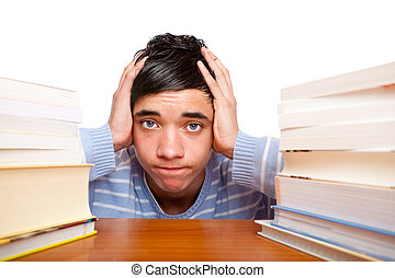 Young handsome male student sitting frustrated between study...