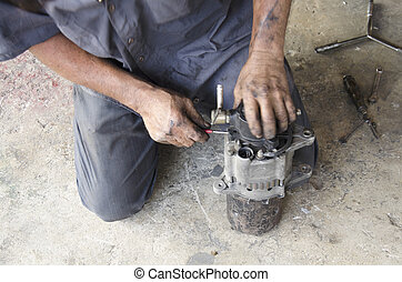 Old man 60 year thai people professional automotive motor mechanic repair and inspecting the alternator in car