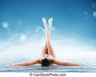 Health and beauty - Woman lying on the water with splashes...